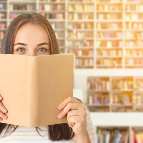 Portrait of beautiful woman with book in modern library