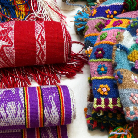 Handicraft souvenirs from Peru - woolen knitted hats and alpaca scarves with tradition design at the international fair on Independence day of Cuenca
